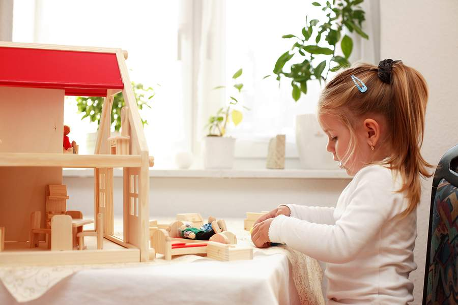 girl playing with wooden dollhouse